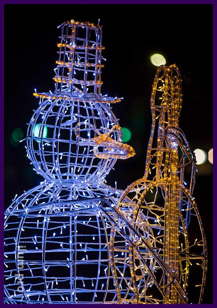 Высокая фигура снеговика с контрабасом из гирлянд