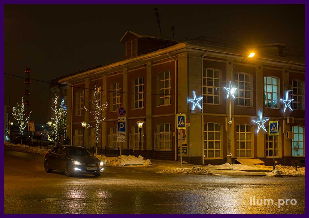 Новогодние гирлянды на фасаде здания и деревьях