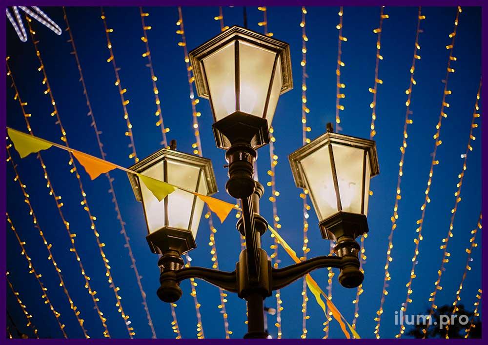 Светодиодные гирлянды и разноцветные флажки над уличным фонарём