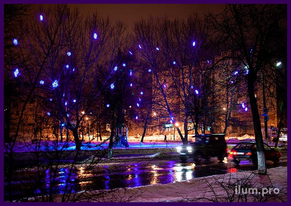 Украшение деревьев в парке светодиодными снежинками