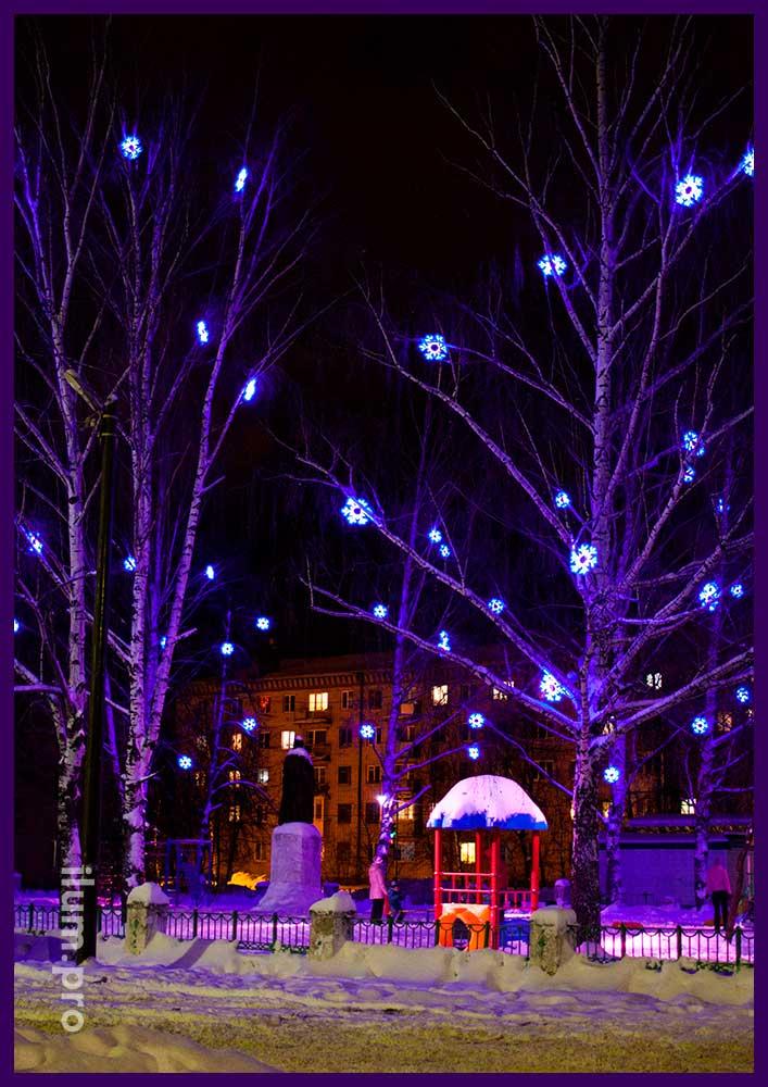 Светодиодные снежинки из шнура на деревьях
