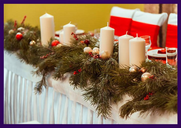 Свечи и натуральная хвоя на новогоднем столе в ресторане