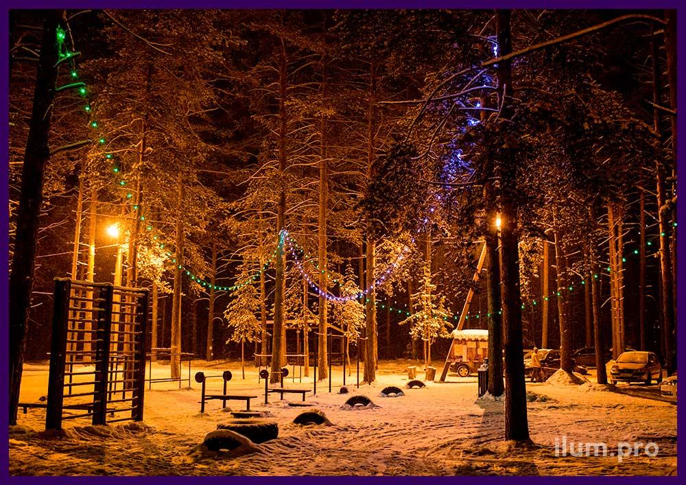 Украшение гирляндами белтлайт белого и зелёного цвета деревьев в парке