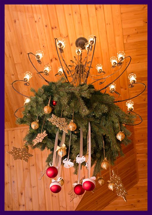 Новогоднее украшение интерьера подвесными декорациями из хвои и ёлочных игрушек