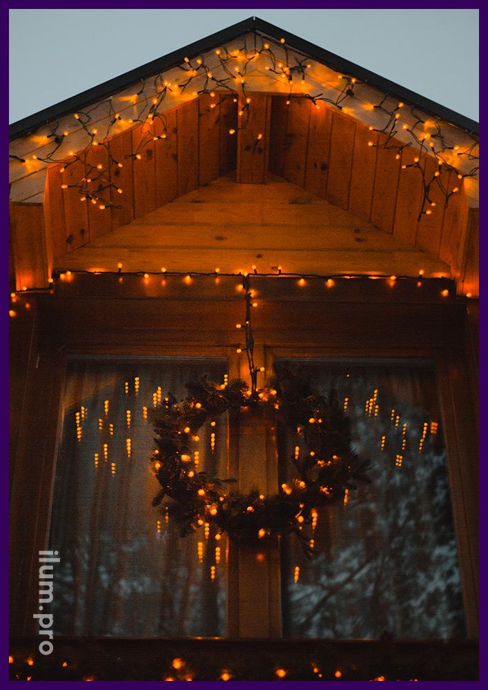 Световое украшение дома гирляндами и рождественский венок