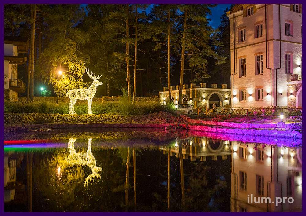 Светящаяся фигура оленя на берегу озера с отражением