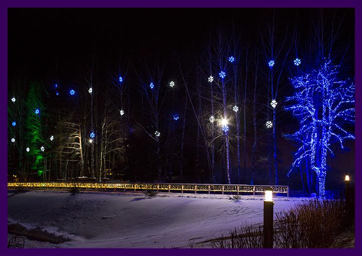 Освещение деревьев разноцветными снежинками
