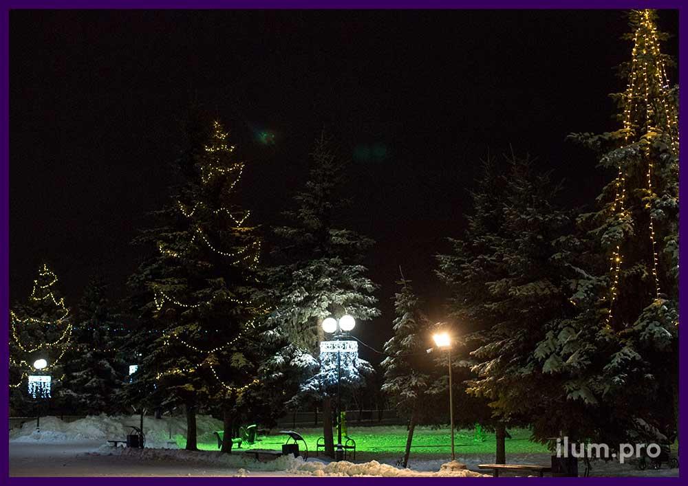 Украшение парка на Новый год гирляндами на фонарях