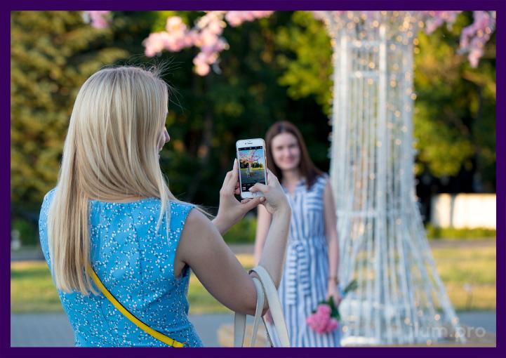 Девушка фотографирует свою подругу на фоне светодиодного дерева с цветами