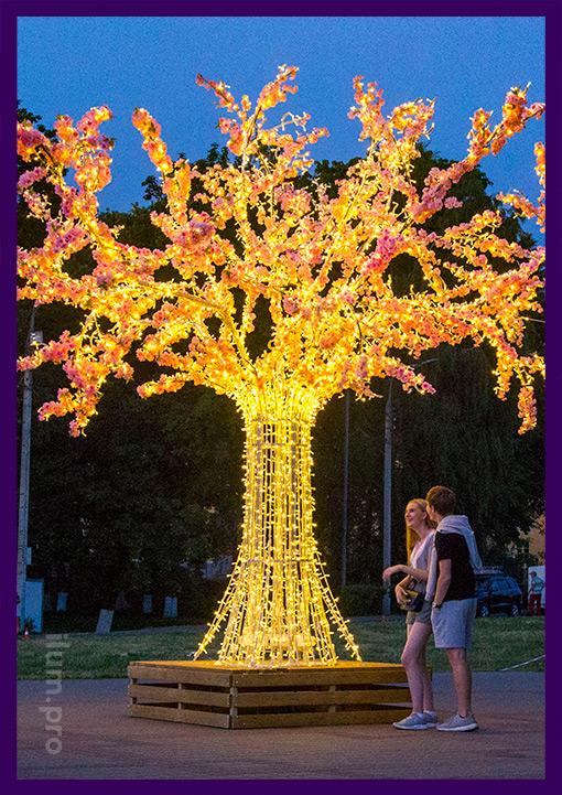 Люди фотографируются на фоне светящегося дерева из металла и гирлянд