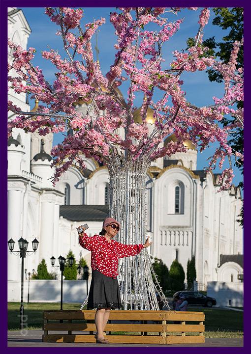 Сакура из алюминия с гирляндами и розовыми цветами. Лавочка в основании.