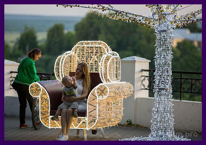 Фигура светодиодная кресло с гирляндами рядом с деревом