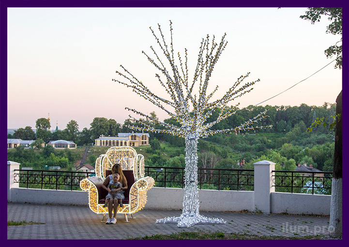 Люди фотографируются на фоне праздничных украшений парка