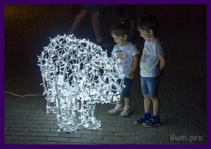 Медведь полигональный с подсветкой гирляндами в парке