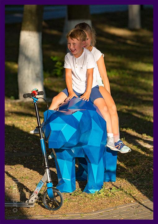 Дети на полигональном медведе из металла в парке
