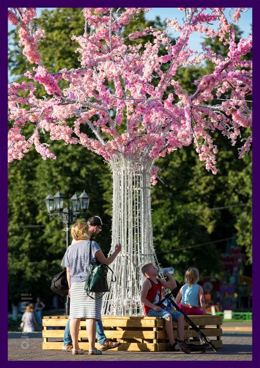 Люди отдыхают на лавочке светодиодного дерева с розовыми цветами