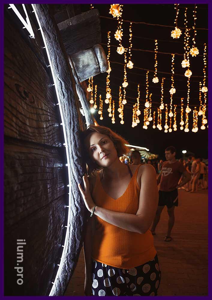 Девушка фотографируется на фоне гирляд в Архипо-Осиповке