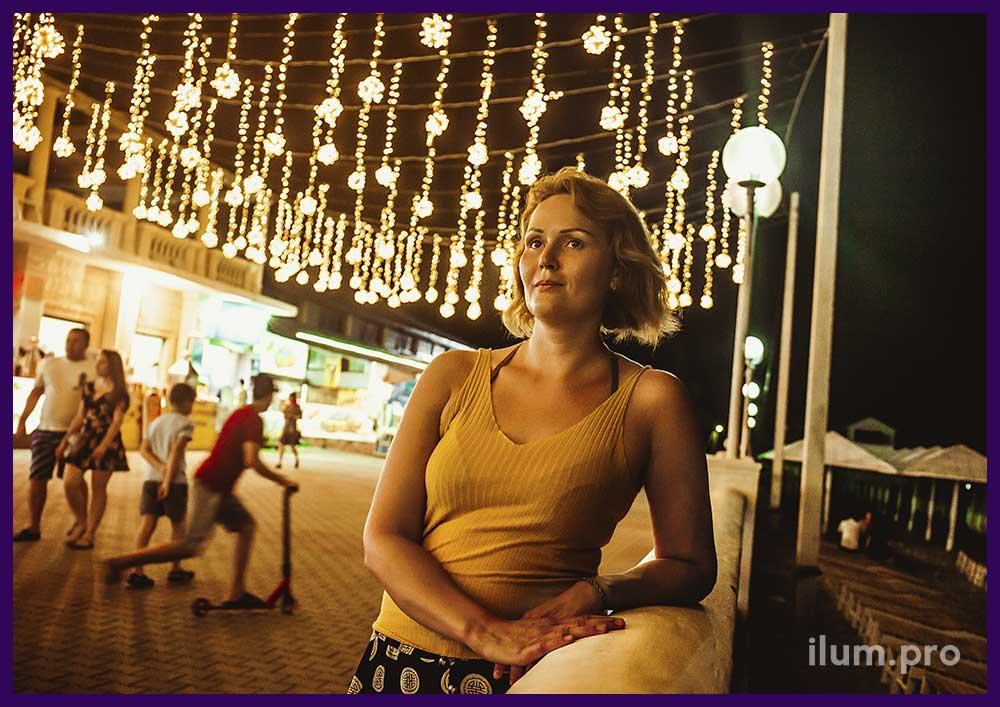 Девушка фотографируется на фоне светодиодных гирлянд