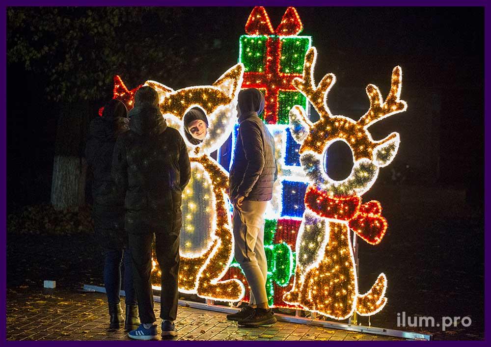 Люди фотографируются рядом с новогодней иллюминацией