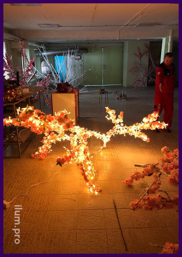 Ветка светящегося дерева с цветами и гирляндами на производстве