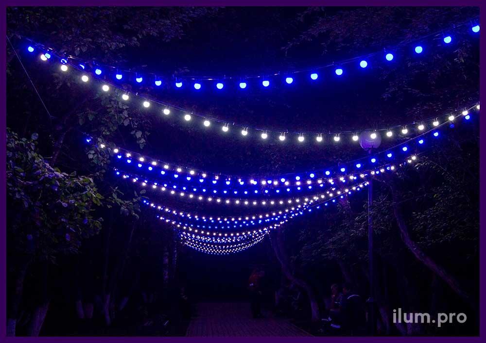 Нитки с лампочками белого и синего цвета над дорогой