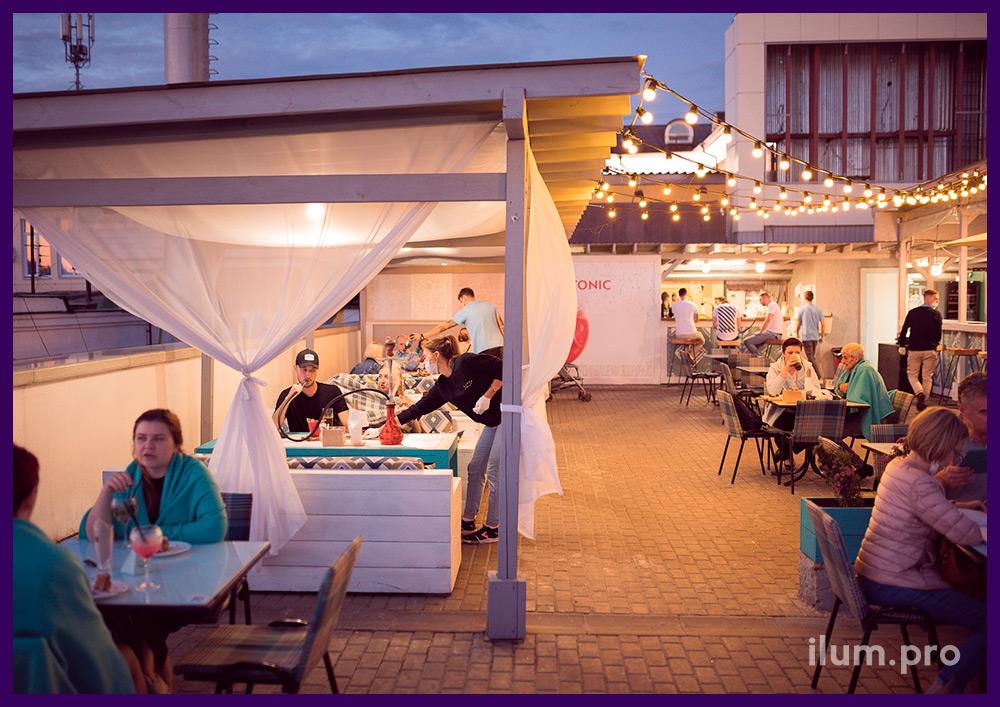 Подсветка территории летнего кафе гирляндами с лампочками белого цвета