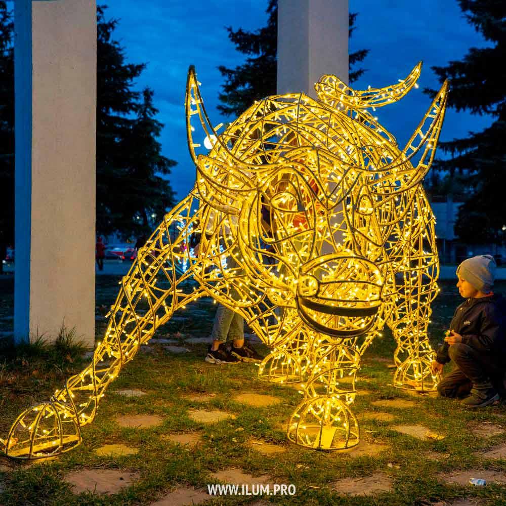 Светящийся символ года – металлический бык с гирляндами в городском парке