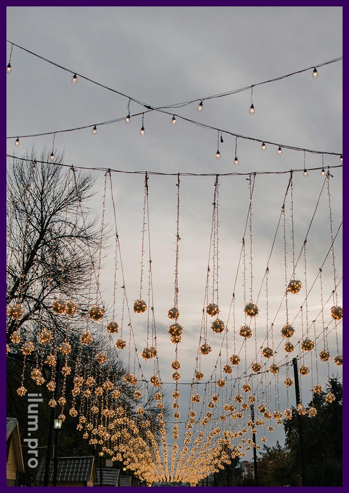 Гирлянды звёздное небо на стальных тросах и ламполайт над дорожкой в парке