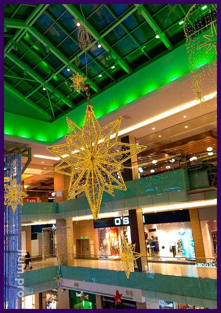 Подсветка атриума торгового центра подвесными фигурами с гирляндами тёплых оттенков