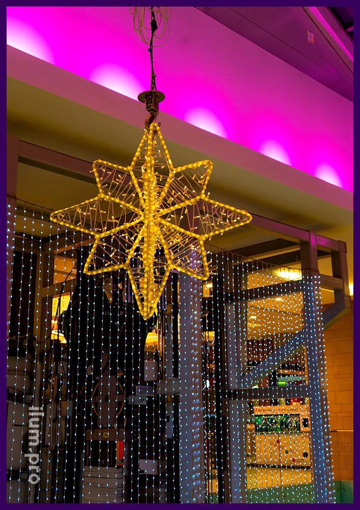 Звёзды и другая иллюминация с металлическим каркасом и гирляндами для украшения атриума торгового центра на Новый год