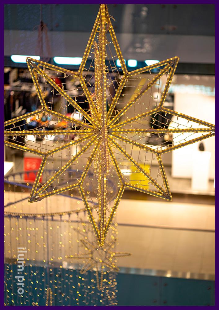 Новогодние украшения атриума подвесными звёздами и композициями в форме цилиндров из светодиодных гирлянд