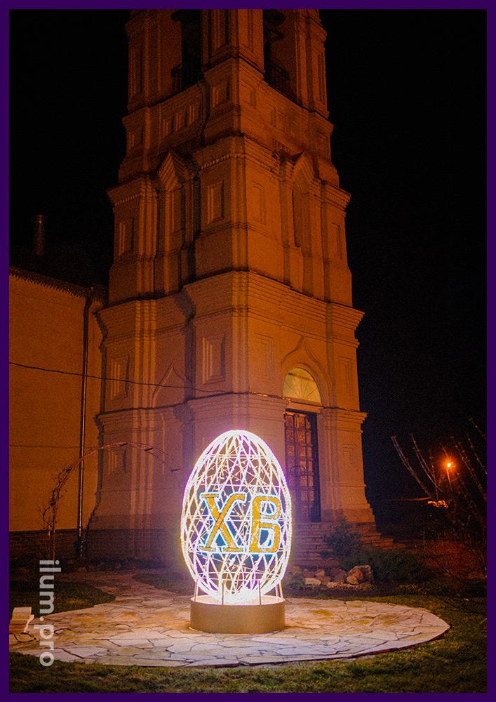 Пасхальные яйца из гирлянд на металлическом каркасе на территории храма во Владимирской области
