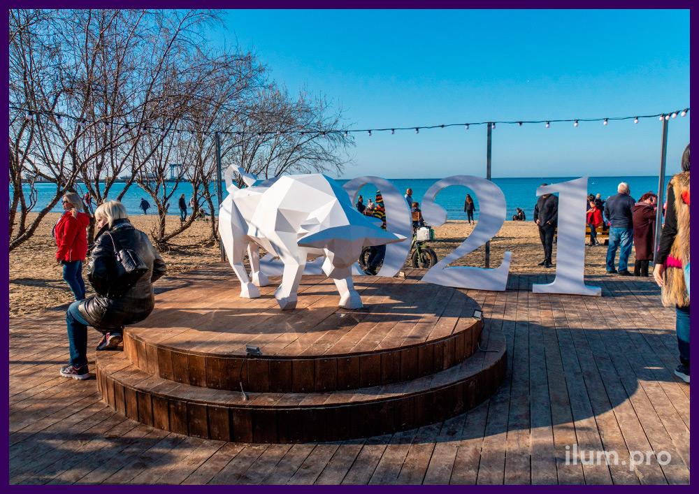 Полигональный бык из крашеной стали на деревянном подиуме на набережной Анапы на Новый год