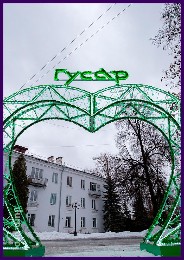 Арка из белых и зелёных гирлянд в форме сердца с логотипом из мишуры на алюминиевом каркасе