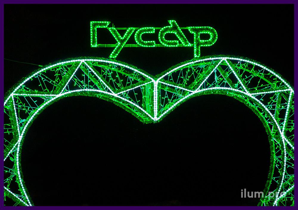 Уличная арка с гирляндами и логотипом заказчика из белых и зелёных гирлянд с дюралайтом