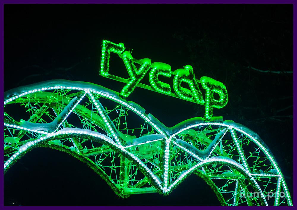 Арка с логотипом компании и зелёными гирляндами в форме сердца на городской площади