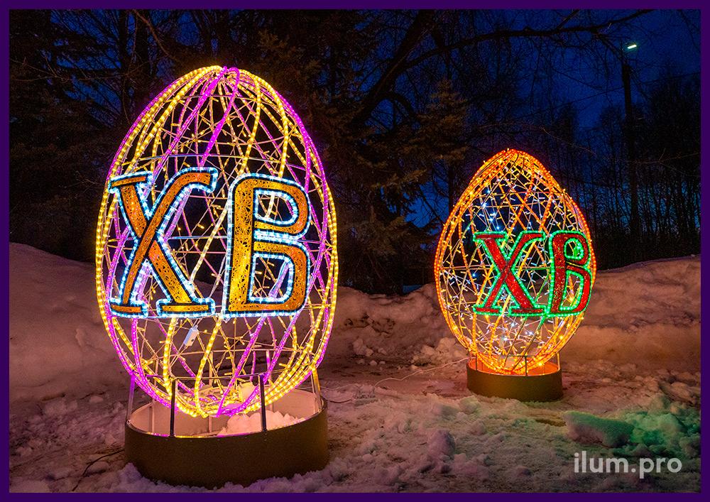 Праздничные пасхальные декорации в форме яиц с буквами ХВ и гирляндами разных цветов