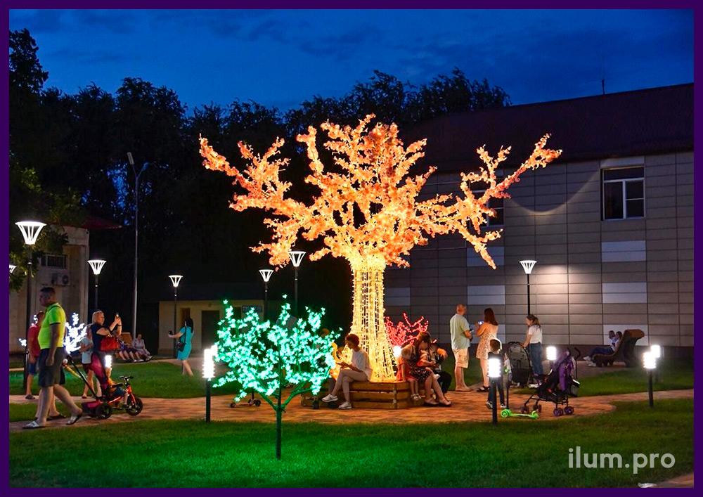Скамейка в парке со светящимся деревом из гирлянд и цветов на алюминиевом стволе и ветках