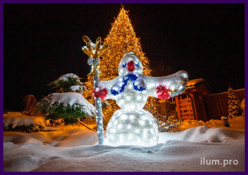 Новогодняя фигура снеговика из алюминиевого каркаса и блестящей мишуры рядом с ёлкой в тёпло-белых гирляндах