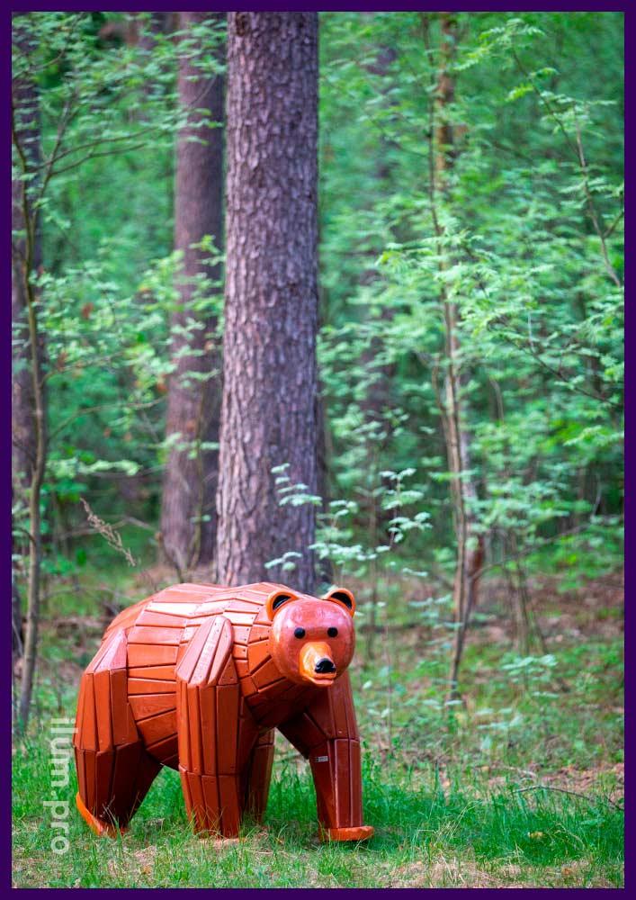 Арт-объект в форме коричневого медведя из крашеного дерева в городском парке