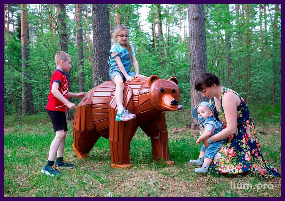Детская фотозона с деревянной фигурой бурого медведя в городском парке
