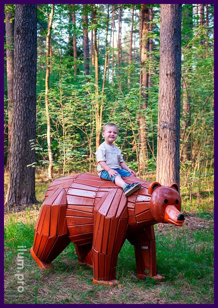 Арт-объект из дерева в парке - медведь коричневого цвета с окрашиванием