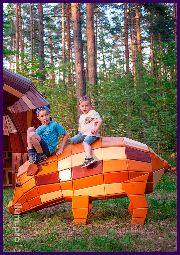 Свинка из разноцветного крашеного дерева - фигура на газоне в парке