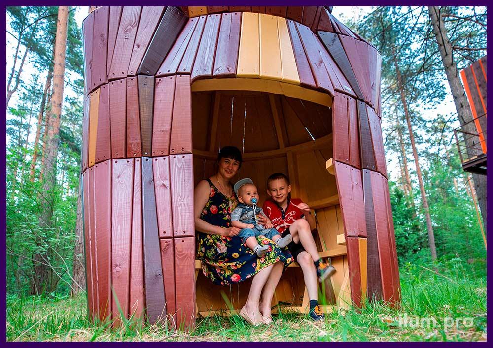 Деревянный домик из разноцветных досок в парке, арт-объект в форме медведицы