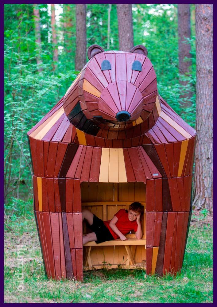 Медведица из дерева хвойных пород со скамейкой внутри - необычный домик в парке