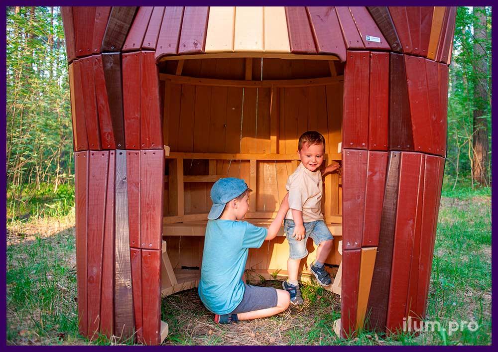 Деревянный домик в парке в форме медведя со скамейкой внутри для детей и взрослых