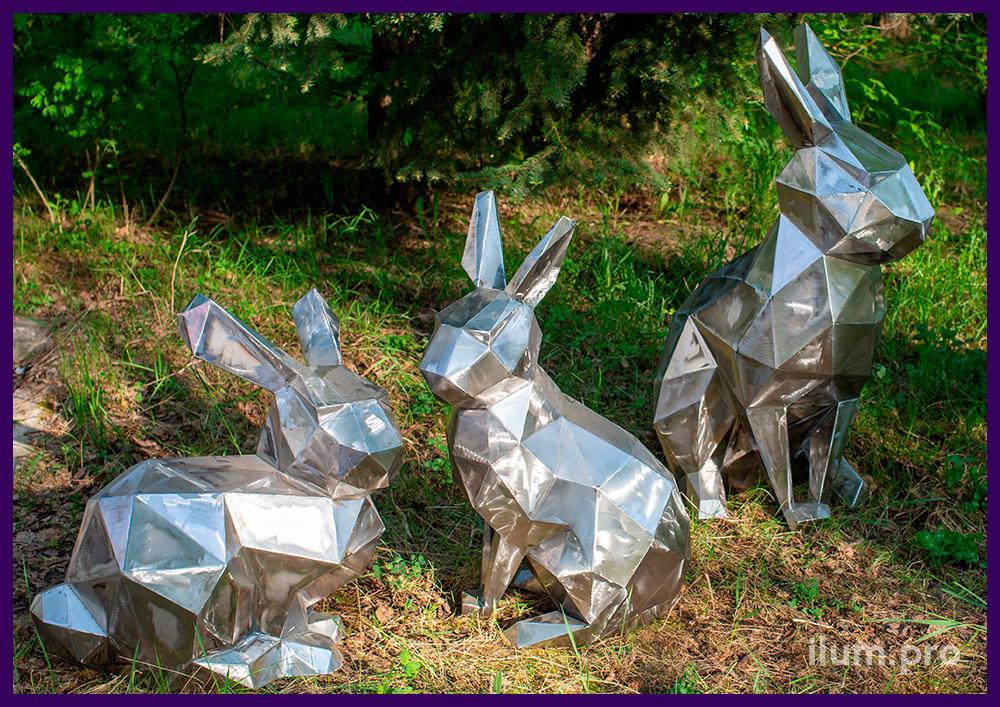 Стальные полигональные зайцы или кролики на траве, у ёлочки, рядом с дорожкой