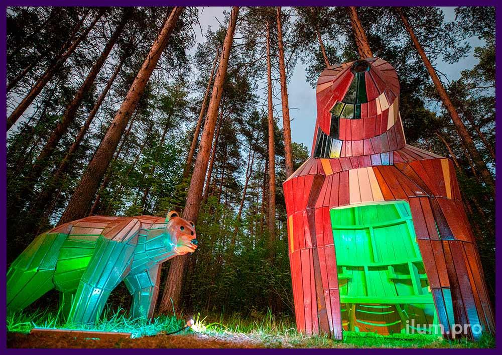 Деревянный домик и арт-объект в форме медведя из дерева в парке