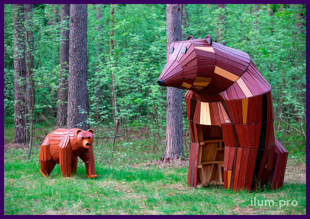 Деревянные фигуры медведей, установленные на лужайке в сосновом лесу