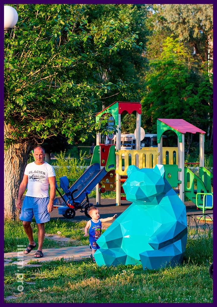 Полигональная фотозона в городском парке, фигура медведя из металла с сине-зелёной краской